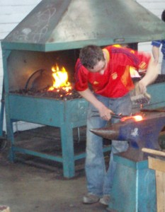 farrier making horseshoe on anvil